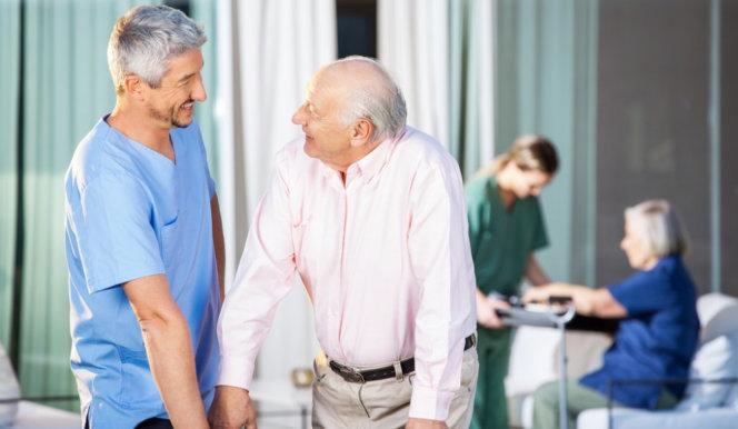 caregiver helping senior man walk with walker
