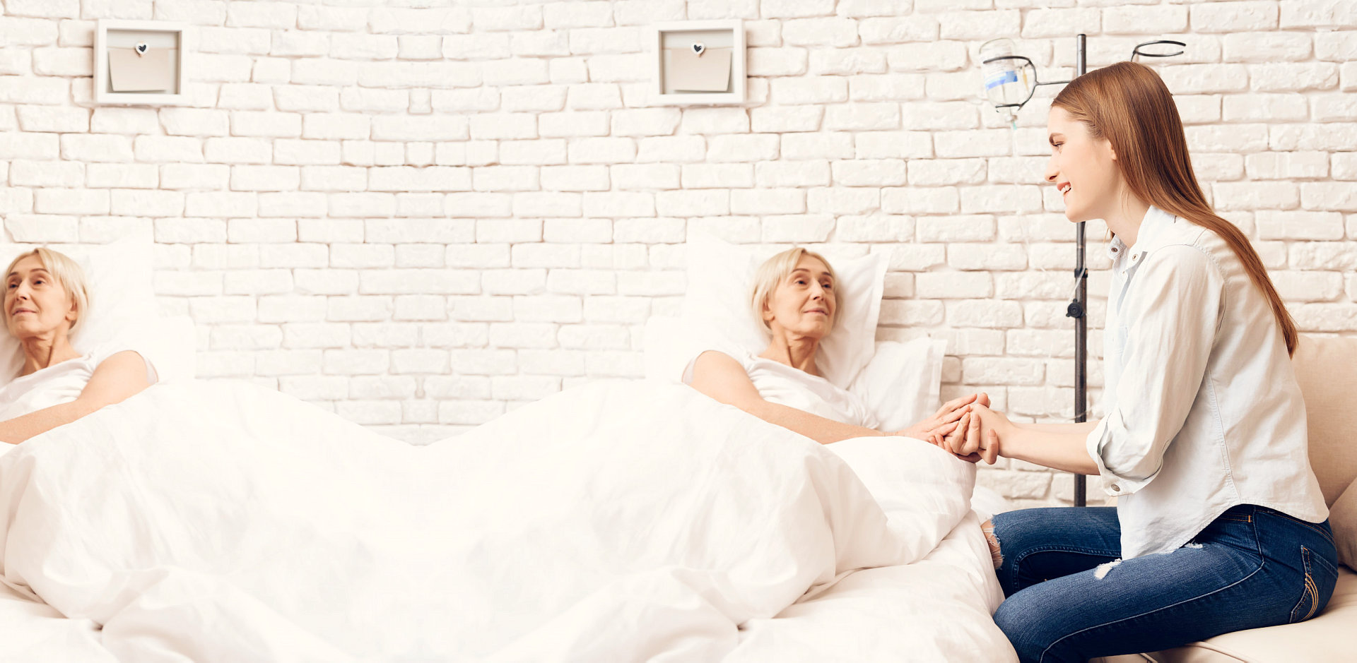 caregiver taking care of senior woman on bed