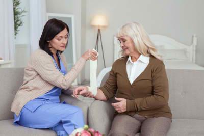 caregiver swathing elder woman hand