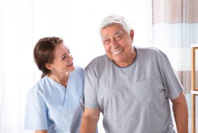 caregiver helping senior man walk