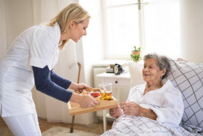 caregiver giving food to a senior woman