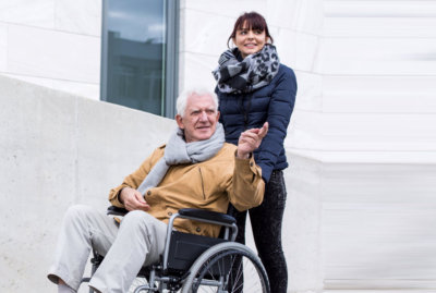 caregiver together with senior man on wheelchair
