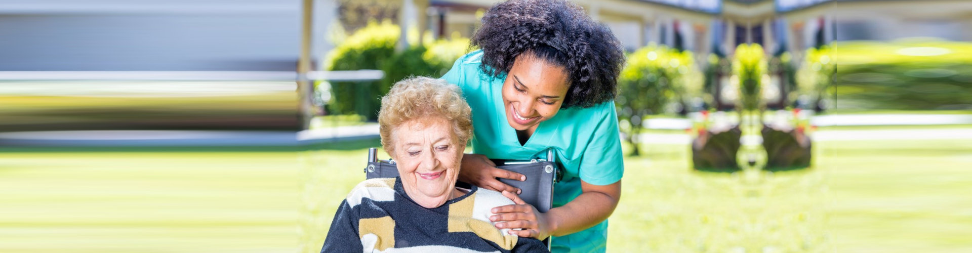 happy caregiver and senior woman on wheelchair outdoor