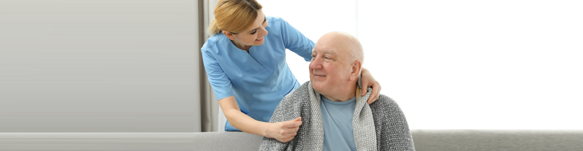caregiver giving blanket to senior man